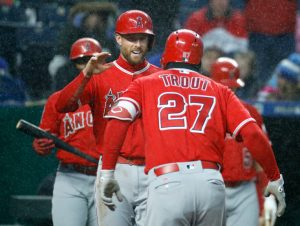 Los Angeles Angels' Mike Trout (27) celebrates with Zack Cozart after hitting a two-run home run during the fifth inning of a baseball game against the Kansas City Royals, Saturday, April 14, 2018, in Kansas City, Mo. (AP Photo/Charlie Riedel)